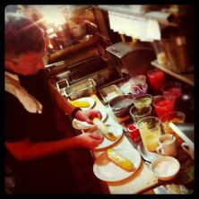 Chef Carmichael prepares dishes behind Mellos cramped counter. (Photo credit: The Mellos Pop-up Facebook page)